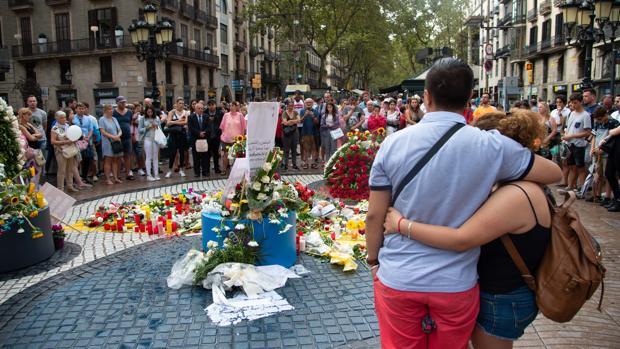Una pareja se abraza frente al mosaico de Miró, en las Ramblas, a la misma hora en la que, hace un año, se produjo el atentado