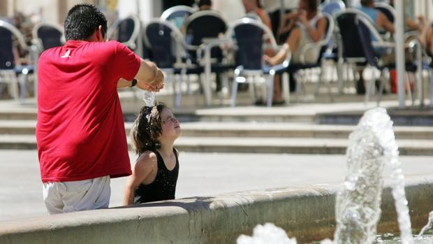 Imagen de un padre refrescando a su hija del calor