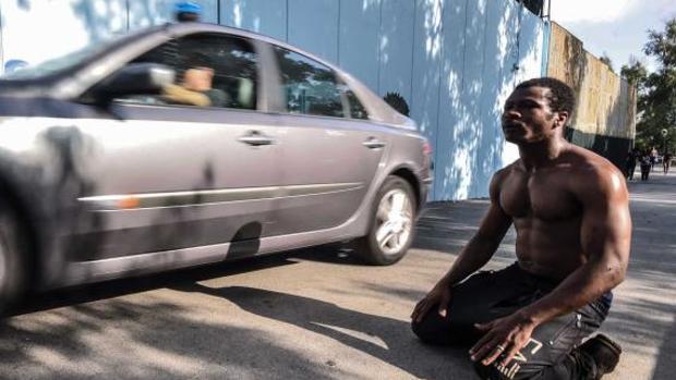 Un inmigrante en Ceuta después del salto de la valla de ayer junto a un coche policial