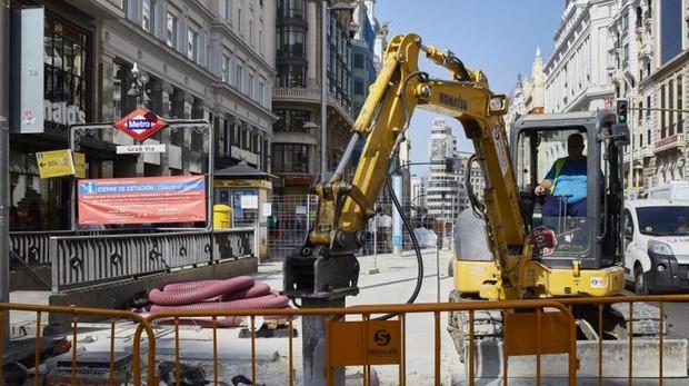 Una excavadora interviene en el pavimento de la Gran Vía a la altura de la calle de Montera