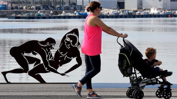 Una mujer paso con un niño pequeño en un carrito junto a una de las esculturas de Miró en Valencia