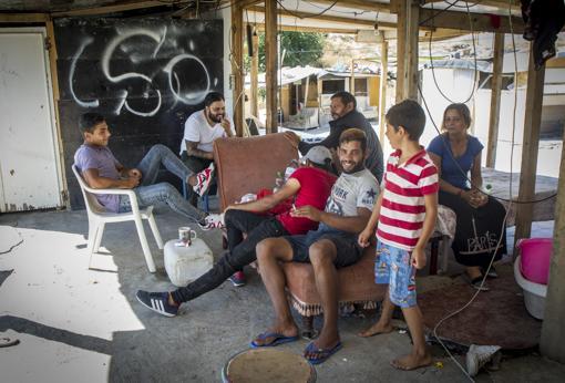 Varios moradores charlan de forma animada en una chabola