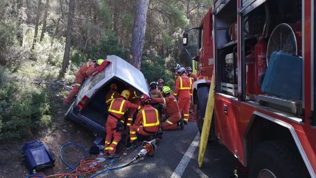 Efectivos de Bomberos rescatando a los dos ocupantes del vehículo, atrapados tras chocar con el árbol