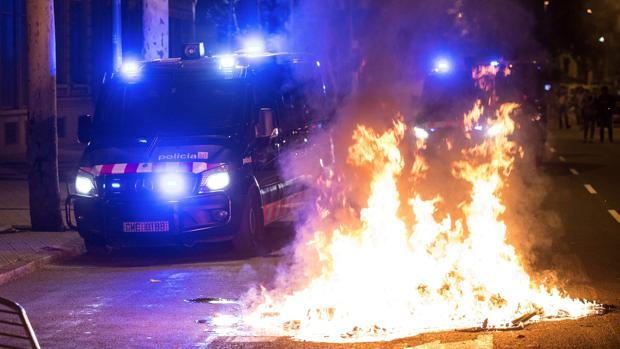 Un furgón de los Mossos d'Esquadra pasa junto al fuego durante los altercados al finalizar la movilización por el aniversario del 1-O
