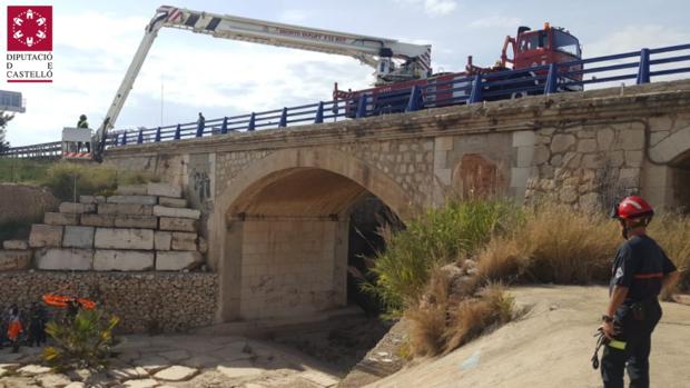 Bomberos durante la maniobra de rescate junto al puente