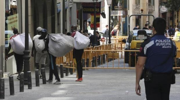 Unos manteros recogen la mercancía ante la presencia policial