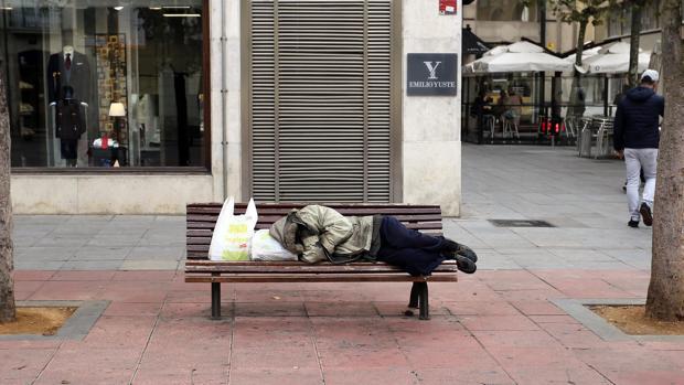 Indigente durmiendo en un banco de la plaza de Santa Ana de Valladolid