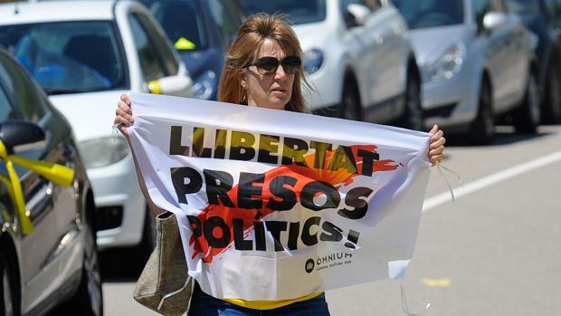 Una mujercon una parcarta a favor de la libertad de los soberanistas presos, en la prisión de Lledoners, en julio