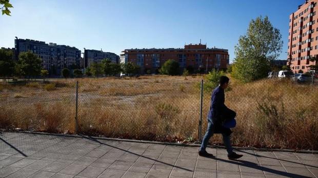 Un hombre camina delante de un solar disponible en Valdecarros