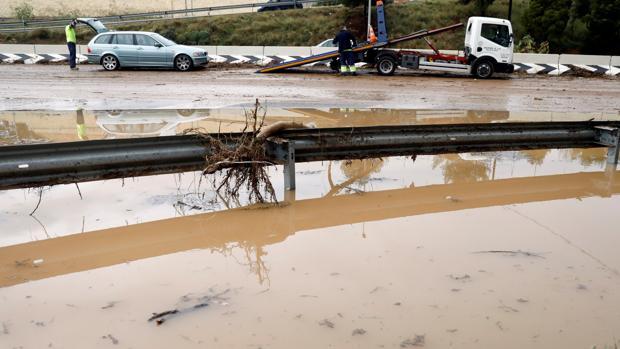 Unos operarios trabajan en la retirada de un vehículo en la CV31 a su paso por Paterna, cortada este viernes por las lluvias