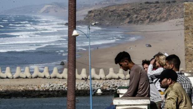 Jóvenes miran la costa desde la que salieron cientos de pateras