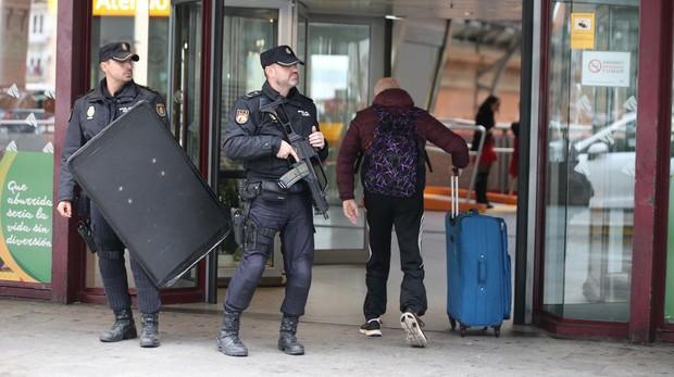 Dos policías armados junto a un viajero en la estación de Atocha