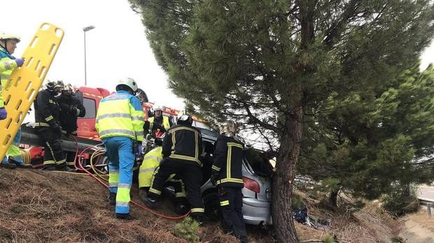 Los bomberos tratan de rescatar al joven en el interior de su vehículo