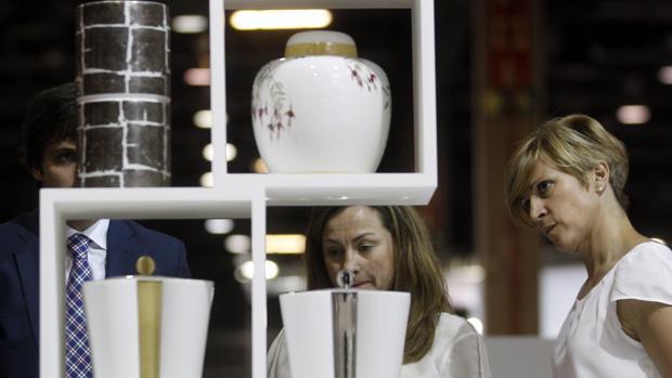 Varias personas contemplan unas urnas funerarias en una imagen de archivo