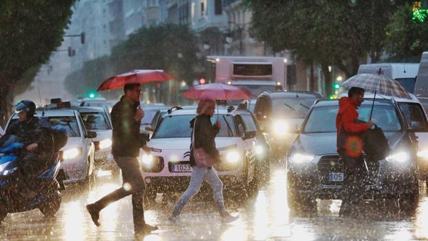 Varias personas se protegen de la lluvia en Valencia