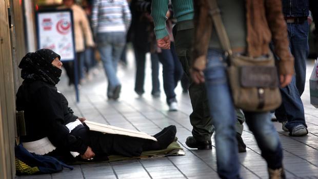 Una mujer pide dinero en una calle de Valencia, en una imagen de archivo