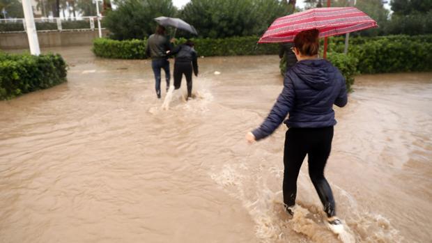 Varias personas cruzan una calle inundada en Valencia el pasado viernes