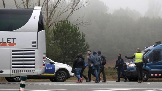 Varios pasajeros suben a un autobús lanzadera habilitado tras el descarrilamiento