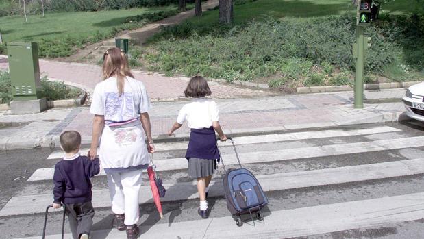 Dos alumnos vestidos con uniforme escolar circulan por un paso de cebra