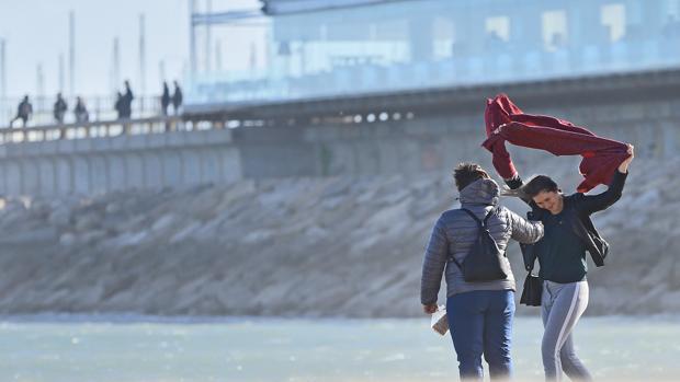 Dos personas se protegen de las fuertes rachas de viento en la playa de Las Arenas de Valencia