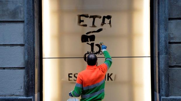 Un operario borra una pintada con el anagrama de la banda terrorista ETA