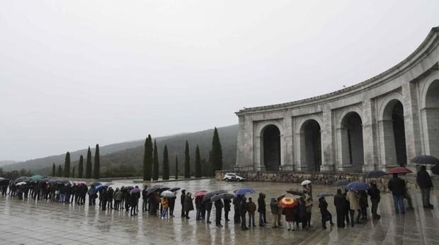 Una larga cola de visitantes aguarda a las puertas del Valle de los Caídos para entrar a la basílica pese a la lluvia