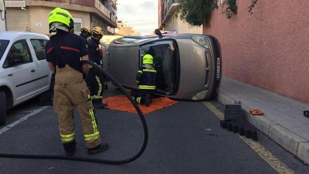Bomberos excarcelando al conductor herido y atrapado en su coche tras volcar