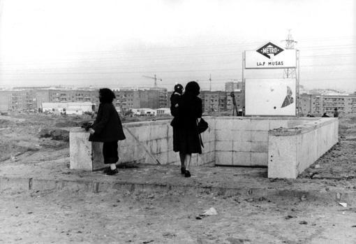 Estación de Metro «Las Musas» en 1975: una viajera se remanga los pantalones para poder llegar a los edificios con el menor barro posible
