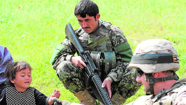 Un militar español da un juguete a un niño en Afganistán
