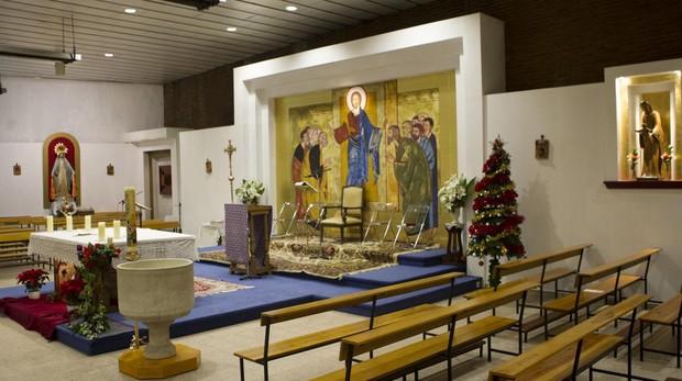 Interior de la parroquia, con un altar presidido por Jesús con los Apóstoles