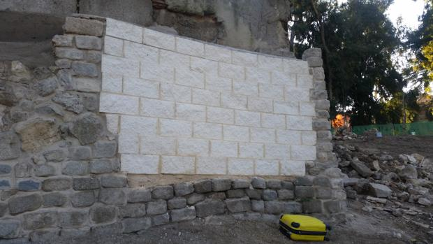 Remates con bloques de hormigón blanco en un muro histórico protegido del siglo XIX, junto al Palacio Real