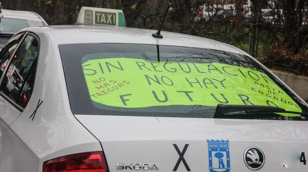 Cartel pidiendo la regulación en uno de los taxis «acampados» en Ifema