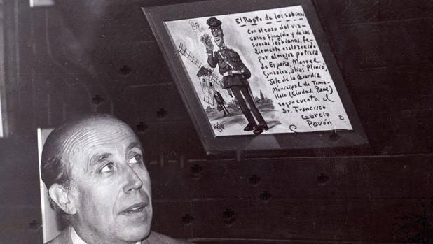 El escritor mira una viñeta que le dedicó el dibujante Antonio Mingote en el diario ABC