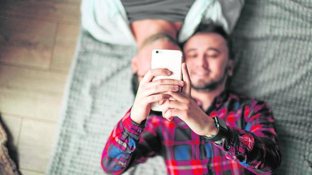 Un hombre tumbado en la cama, junto a otro, mira su móvil
