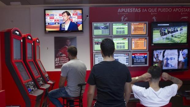 Jóvenes viendo un partido de fútbol en una casa de apuestas