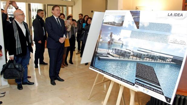 El presidente Puig junto a una imagen de la zona portuaria donde se construirá el nuevo edificio con forma de cubierta del barco