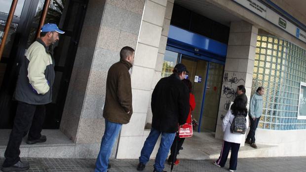 Un grupo de personas espera a las puertas de las Oficinas de Empleo en Santiago