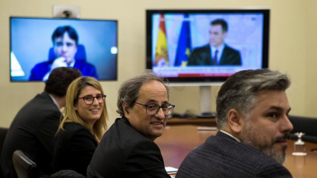 Los dirigentes de Junts per Catalunya con pantallas en las que aparecen Pedro Sánchez y Carles Puigdemont