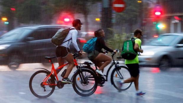 Ciclistas circulando por Valencia bajo la lluvia