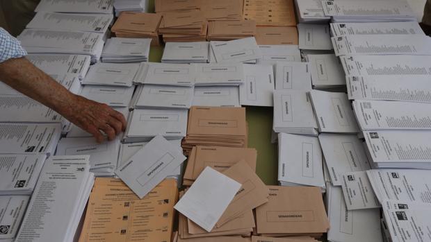 Un elector recoger una papeleta en una mesa electoral