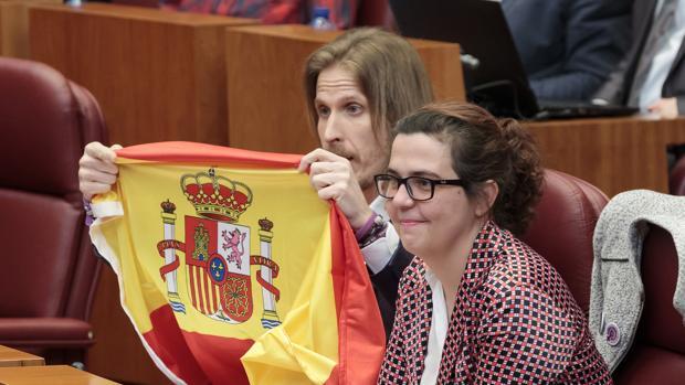 El líder de Podemos en Castilla y León, Pablo Fernández, muestra a Herrera la bandera de España