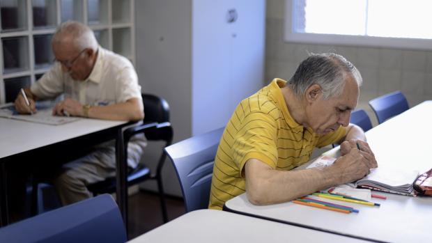 Usuarios de un centro de día leyendo y haciendo ejercicios