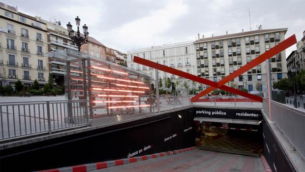 Entrada al parking de la plaza de Pedro Zerolo, con el lazo rojo diseñado por Teresa Sapey