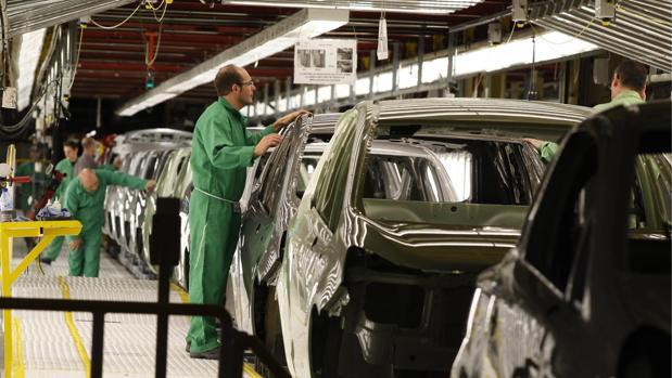 Operarios en una cadena de montaje de la factoría de Opel en Figueruelas (Zaragoza)