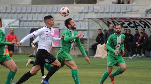 Pablo Aguilera, de blanco y negro, persigue un balón