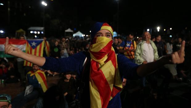 Una independentista insulta a España en la jornada del 1-O, mientras oculta su rostro con una «estelada»