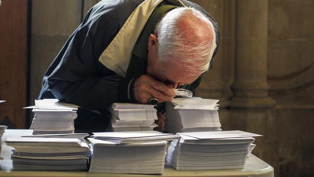Un ciudadano mirando con lupa las papeletas dispuestas en un colegio electoral