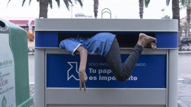 Imagen de archivo de un menor no acompañado entrando en el contenedor en el que duerme, en Melilla