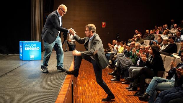 El presidente del PP de Orense, Manuel Baltar, ayuda a Feijóo a subir al escenario en Celanova