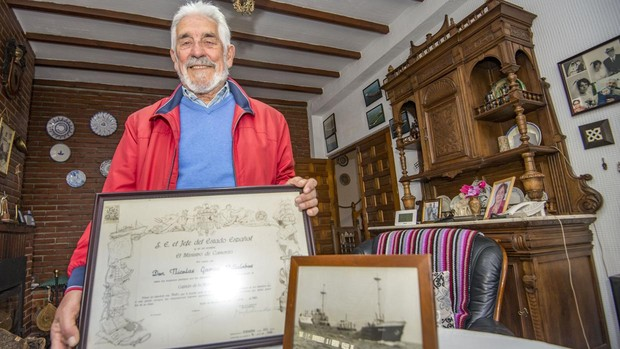 Nicolás sujeta su título de Naútica jutno con un cuadro del barco «Mirenchu» donde pasó la luna de miel